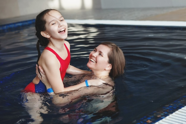 Mother and daughter playing in the pool with blue water