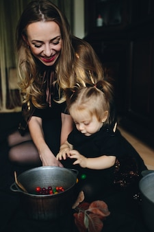 Mother and daughter playing together at home on halloween