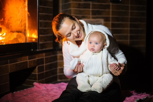 Mother and daughter playing together near fireplace