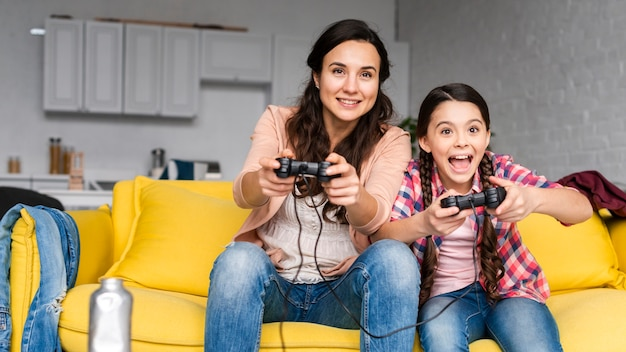 Mother and daughter playing video games together