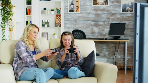 Mother and daughter playing video games using wireless controller sitting on the couch.