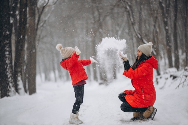 Mother and daughter playing in winter park