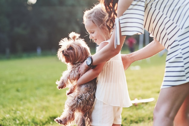 Mother and daughter playing with cute dog outside in the green grass