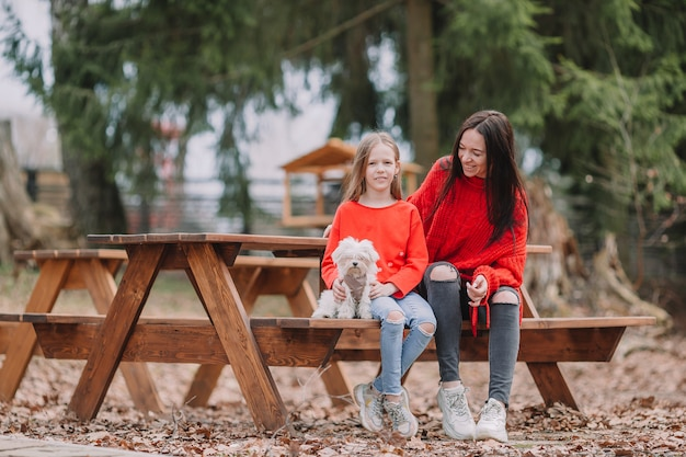 Mother and daughter playing with dog outdoors