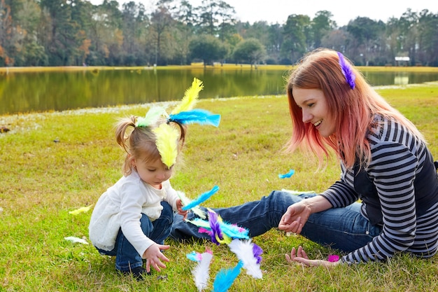 Mother and daughter playing with feathers in park