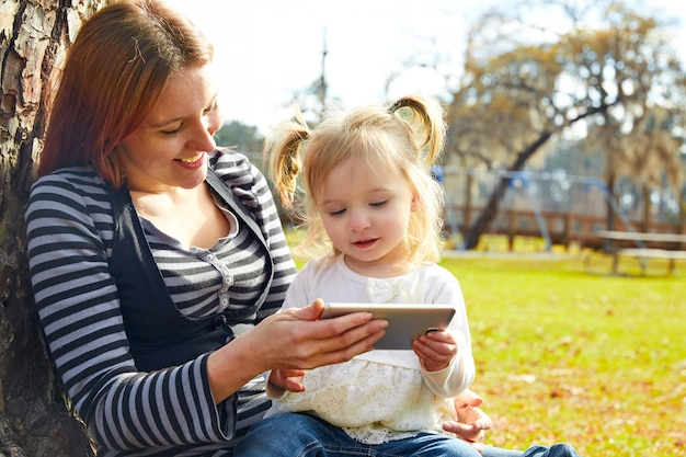 Mother and daughter playing with smartphone