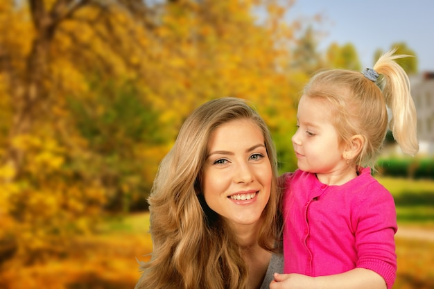 Mother and daughter portrait in autumn park