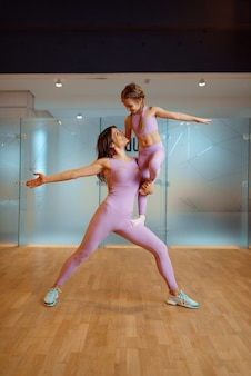 Mother and daughter poses in gym, healthy lifestyle, fitness workout. mom and little girl in sportswear, woman with kid on joint training in sport club