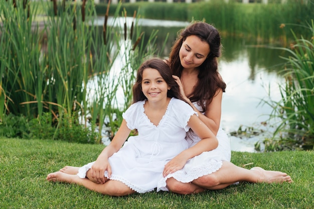 Mother and daughter posing outdoors