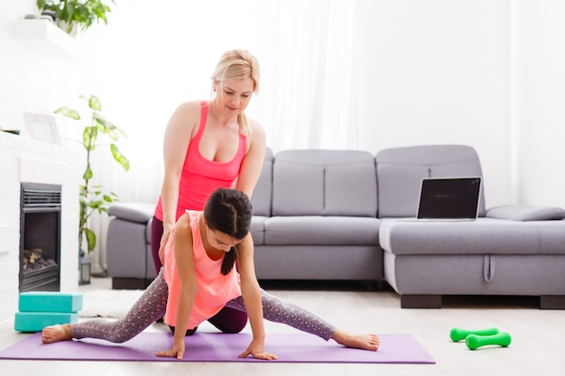 Mother and daughter practicing online yoga lesson at home