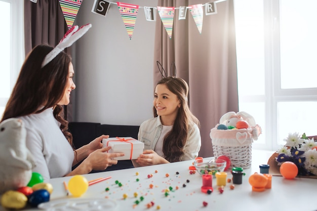 Mother and daughter prepare for easter in lovely room. they hold present together. young woman and girl look at each other and smile. decoration and eggs on table.