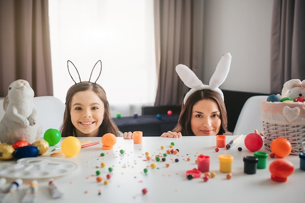 Mother and daughter prepare for easter. they hide behind table with decoration, eggs and painting on it. mother and daughter look straight and smile. they wear bunny ears.
