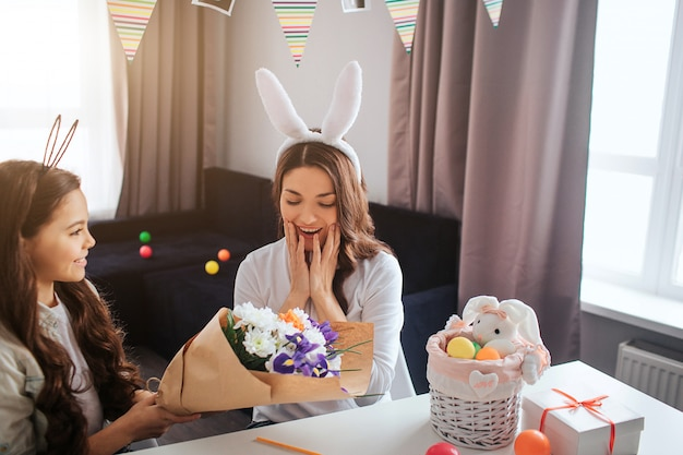 Mother and daughter prepare for easter together. girl give beautiful bouquet of flowers to her mother. she looks amazed. basket and present on table.