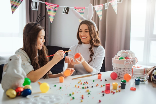 Mother and daughter prepare for easter. young woman wear rabitt ears and hold egg. girl painting it. they have fun together. daylight.