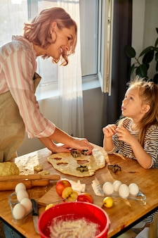 Mother and daughter prepare flour baked goods on a table in the kitchen at home