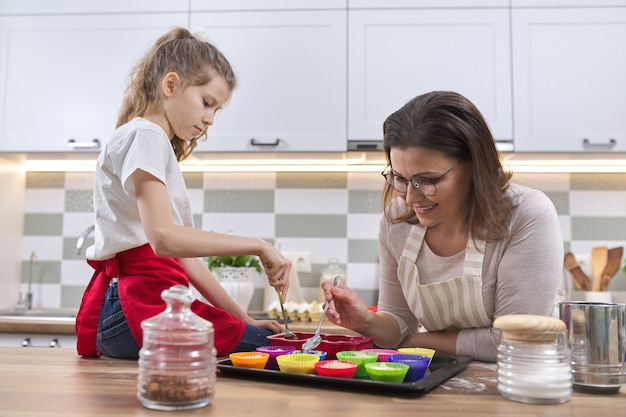 Mother and daughter preparing cupcakes together at home in kitchen