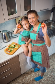 Mother and daughter preparing a salad meal in the kitchen at home