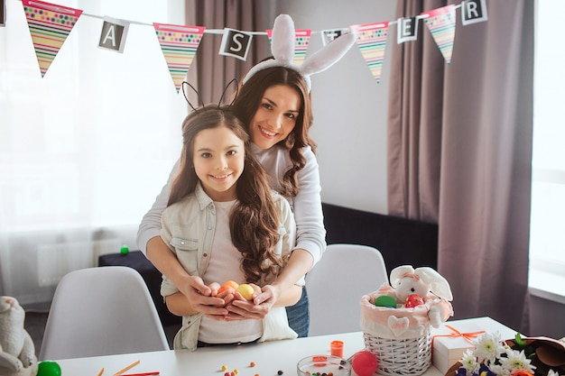 Mother and daughter prespare for easter in room. they stand and hold colorful eggs in hands. people look on camera and smile. festive and happy.