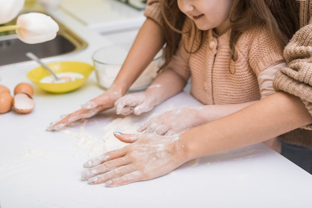 Mother and daughter putting flour on table