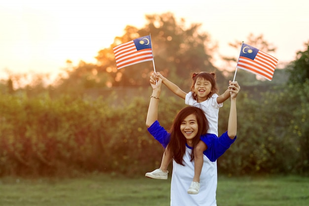 Mother and daughter raising flag of malaysia