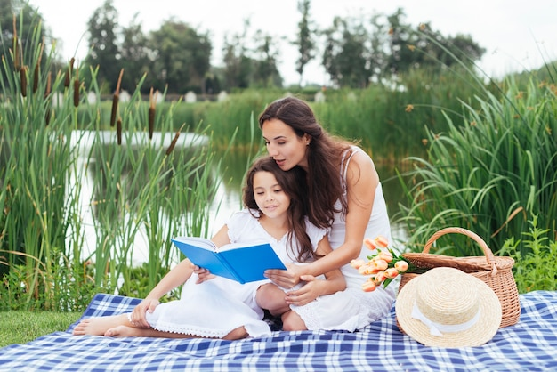 Mother and daughter reading book by the lake