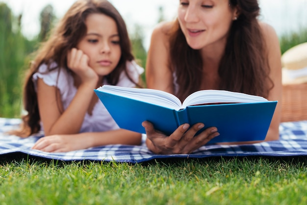 Mother and daughter reading book outdoors