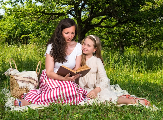 Mother and daughter reading a book in the park. family time