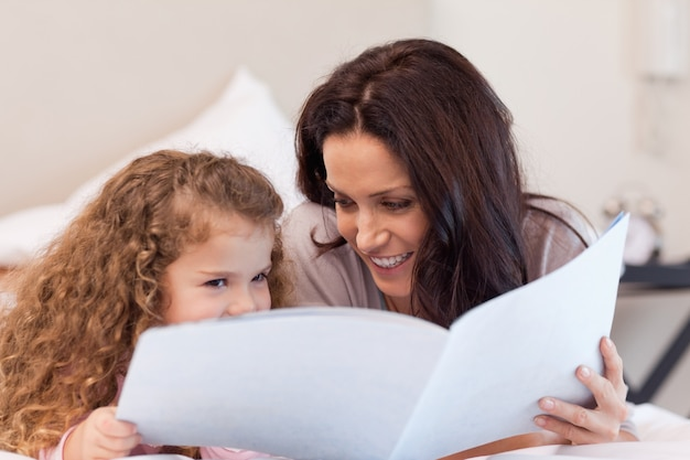 Mother and daughter reading a book together