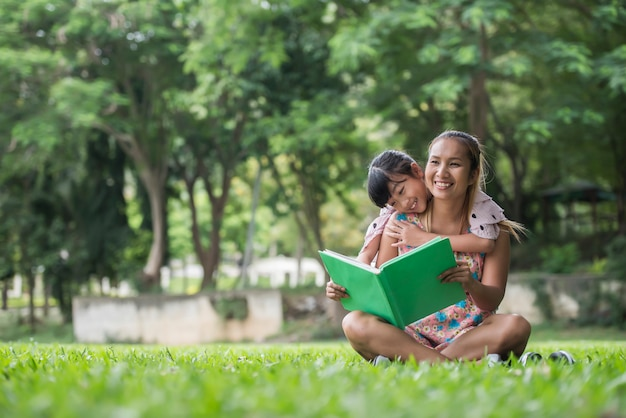 Mother and daughter reading a fairytale to her daughter in the park