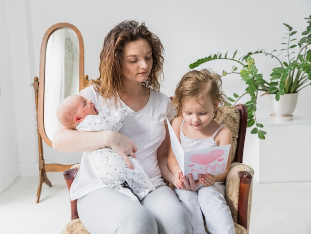 Mother and daughter reading greeting card together sitting on arm chair in home holding baby