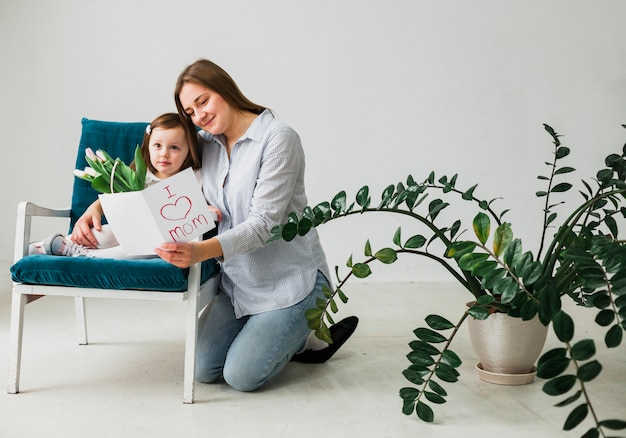 Mother and daughter reading greeting card