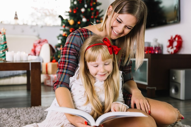 Mother and daughter reading in living room