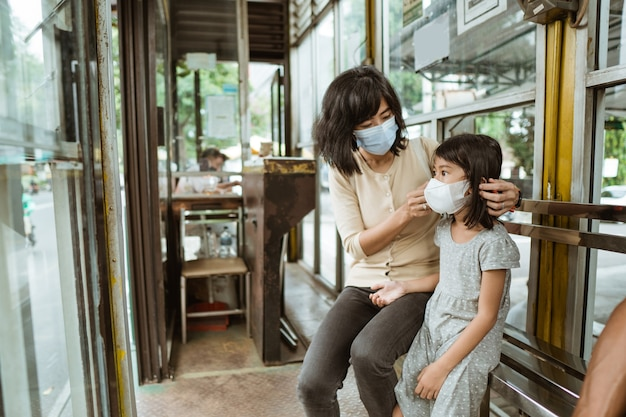 Mother and daughter riding public transport during pandemic wearing facemask