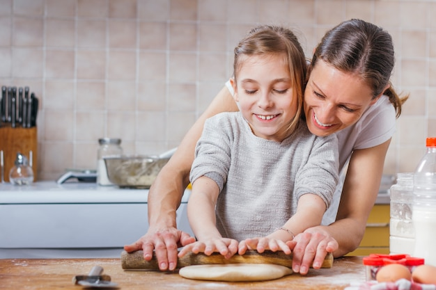 Mother and daughter rolling dough with rolling pin