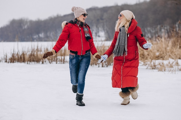 Mother and daughter running on lake in winter time