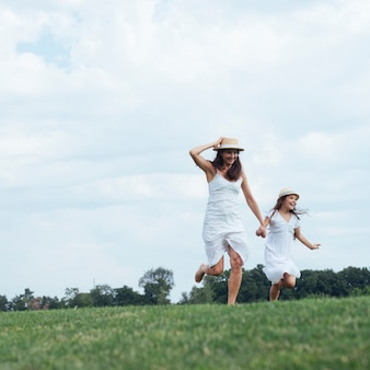 Mother and daughter running outdoors