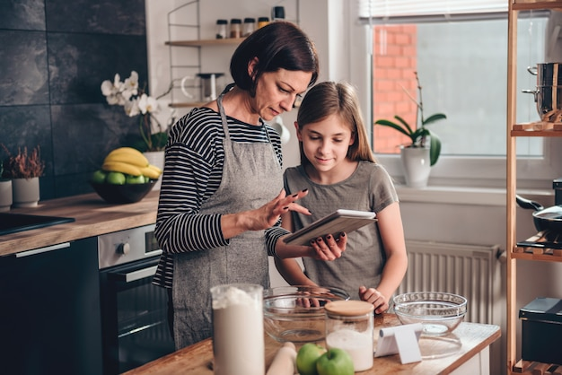 Mother and daughter searching apple pie recipe on the tablet