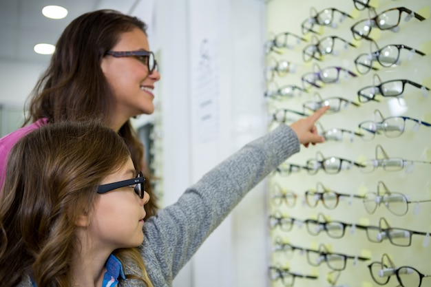 Mother and daughter selecting spectacles from display
