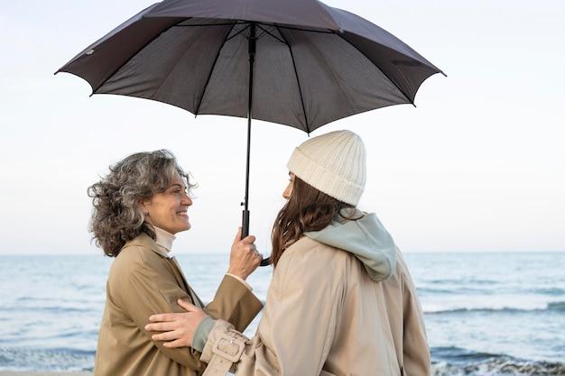 Madre e figlia condividono un tenero momento mentre sono in spiaggia sotto l'ombrellone