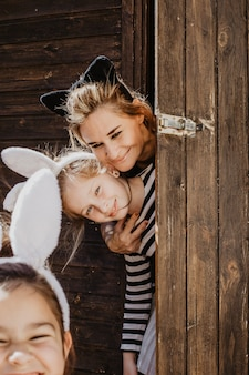 Mother and daughter behind shed door