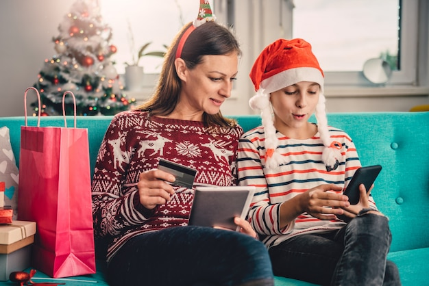 Mother and daughter shopping online at home during christmas