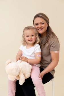 Mother and daughter showing sticker on arm after getting a vaccine