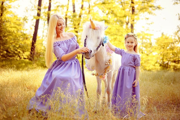 Mother and daughter in similar lavender dresses are petting a un