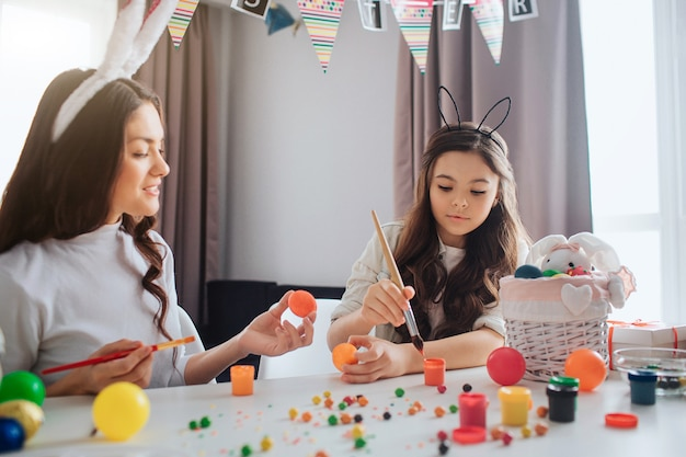 Mother and daughter sit at table and prepare for easter. they painting eggs. girl reach paint with brush. young woman hold orange egg.