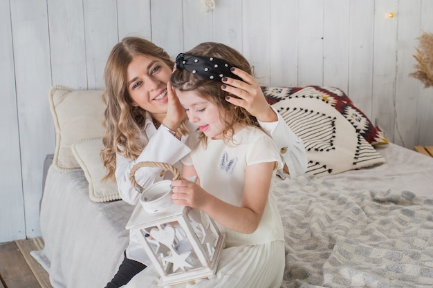 Mother and daughter sittig on bed with lattern for candle.