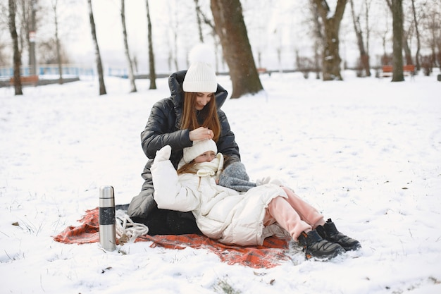 Mother and daughter sitting on a blanket on snowy park