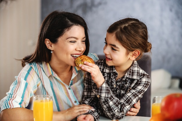 Mother and daughter sitting at dining table together and having healthy breakfast