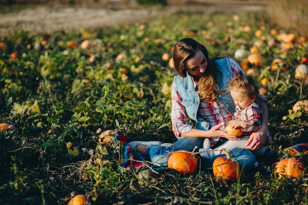 Mother and daughter sitting in a field of pumpkins