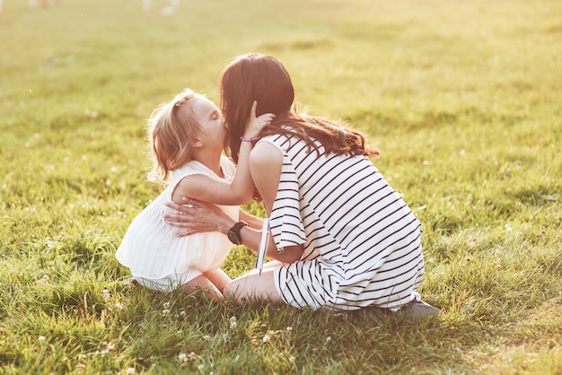 Mother and daughter sitting on the grass of the field and kiss each other