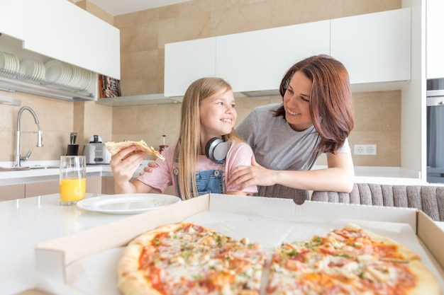 Mother and daughter sitting in the kitchen, eating pizza and having fun